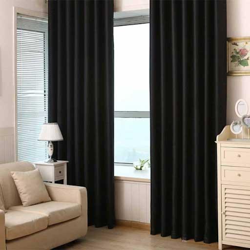 Rèm vải trơn màu đen nổi bật giữa những món đồ nội thất màu kem.